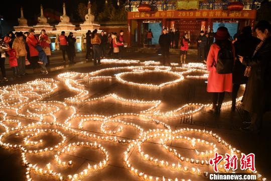 民众在西安广仁寺点亮酥油灯祈福新春。 田进 摄